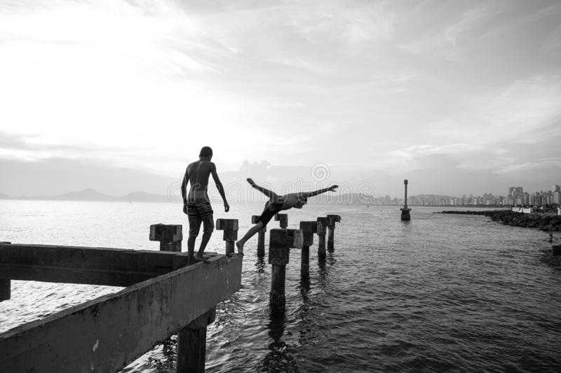 Two needy boys playing jump in the sea from an old pier destroyed royalty free stock photos