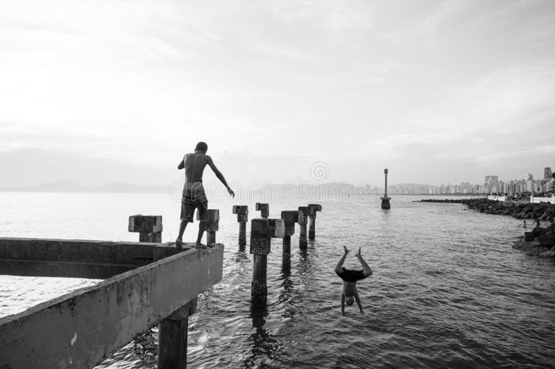 Two needy boys playing jump in the sea from an old pier destroyed stock photos