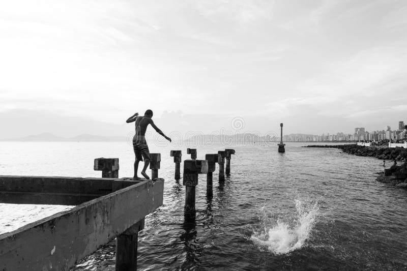 Two needy boys playing jump in the sea from an old pier destroyed stock photography