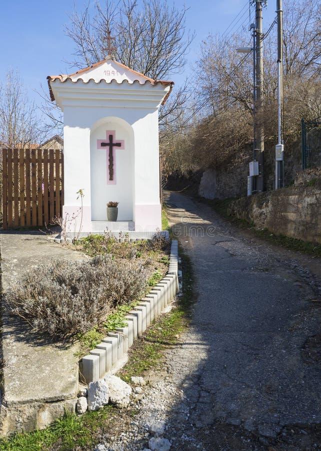 Santuário branco pequeno do wayside, bênção da estrada ou tortura dos deuses com a curva seguinte transversal da estrada da v foto de stock