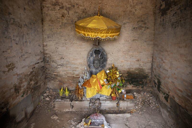 Santuário budista com a estátua de pedra da Buda sob o guarda-chuva amarelo com ofertas Altar budista tradicional foto de stock royalty free