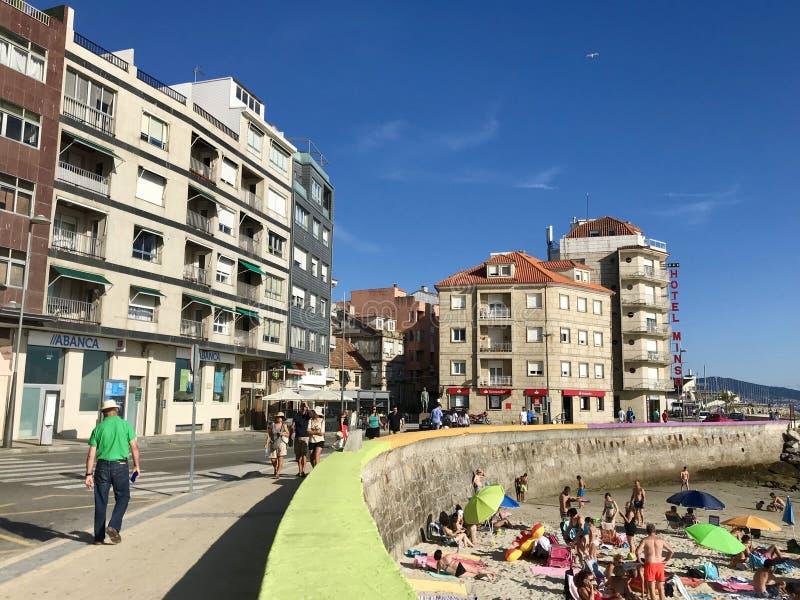 Sanxenxo, Pontevedra / Spain - July 26 2018: View of the beachfront of Sanxenxo with some people walking on the promenade near royalty free stock photography