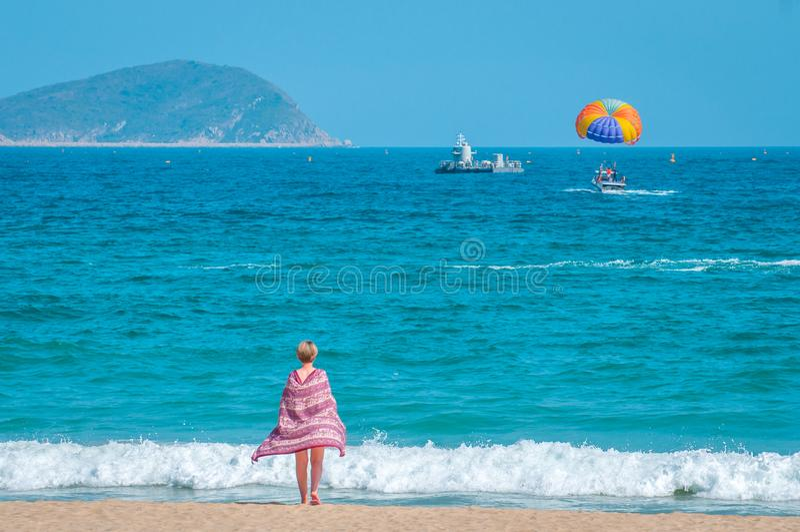 Sanya, baía de Yalong, Hainan, China - 14 de maio de 2019: Praia limpa bonita Uma jovem mulher anda ao longo do litoral arenoso imagens de stock royalty free