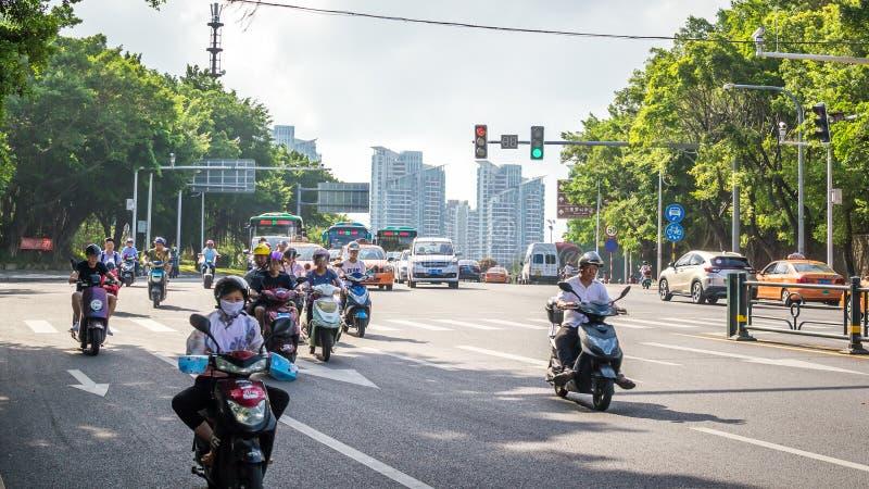 Sanya, China - May 15, 2019: Road traffic. A lot of electric cars. Hybrid buses. 90 percent of mopeds are electric. Sanya, Hainan island, China - May 15, 2019 stock image