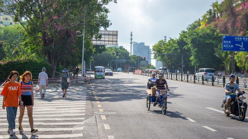 Sanya, China - May 15, 2019: Road traffic. A lot of electric cars. Hybrid buses. 90 percent of mopeds are electric. Sanya, Hainan island, China - May 15, 2019 stock photo