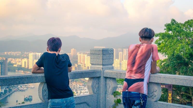 Sanya, Hainan, China - 16 de mayo de 2019: dos individuos no identificados jovenes miran el panorama de Sanya fotografía de archivo libre de regalías