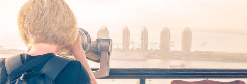 Sanya, Hainan China. A girl is watching through binoculars a panorama of Sanya Phoenix Island. Sunset, blur, haze royalty free stock image