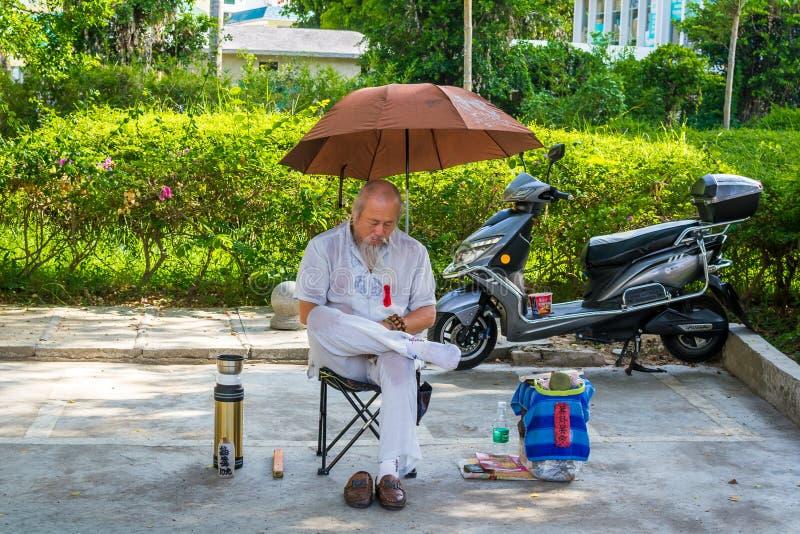 Sanya, Hainan, Chiny - 16 Maj: 2019: Na gorącym dniu, nieprzyzwyczajony chińczyk w ulicie siedzi pod parasolem i śpi obrazy stock