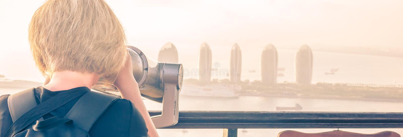 SANYA, HAINAN CINA Una ragazza sta guardando tramite il binocolo un panorama di Sanya Phoenix Island Tramonto, sfuocatura, foschi immagine stock libera da diritti