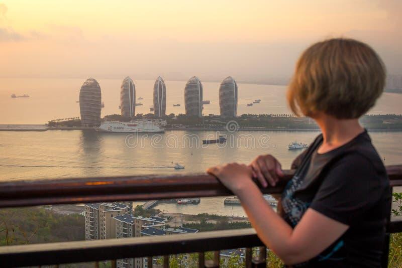 Sanya, Hainan-eiland, China - Mei 16, 2019: Een meisje let op een panorama van Sanya Phoenix Island Zonsondergang, onduidelijk be royalty-vrije stock afbeeldingen