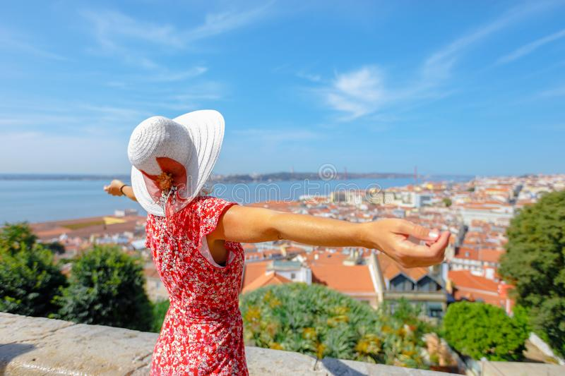 Sao Jorge Castle overlook. Happy woman with open arms admiring 25 April Bridge, Tagus river and Baixa District from Sao Jorge Castle in Alfama, Lisbon, Portugal royalty free stock photography
