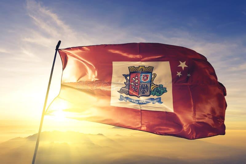Sao Jose of Brazil flag waving on the top sunrise mist fog. Sao Jose of Brazil flag textile cloth fabric waving on the top sunrise mist fog royalty free stock image