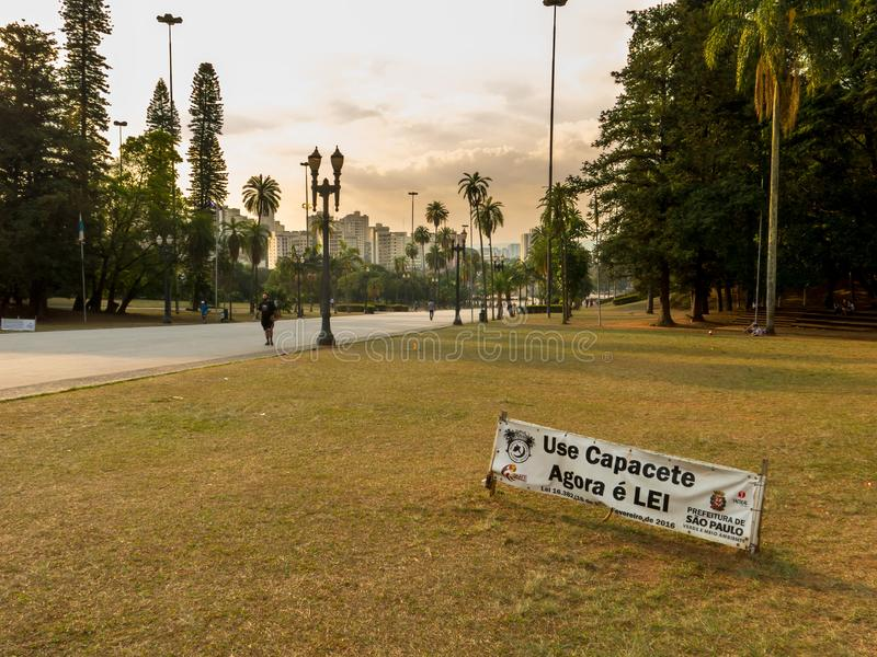 Information band about helmet mandatory use for skateboarders in Independence park in Sao Paulo. SAO PAULO, BRAZIL - JUL 05, 2018 - Information band about helmet royalty free stock photography