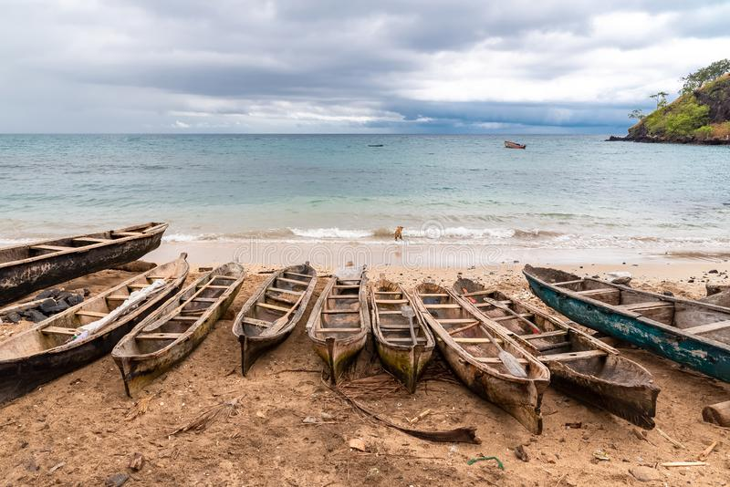 Sao Tome, wooden dugouts. Sao Tome, traditional wooden dugouts on the beach in a fishermen`s village, a dog in the sea stock photo