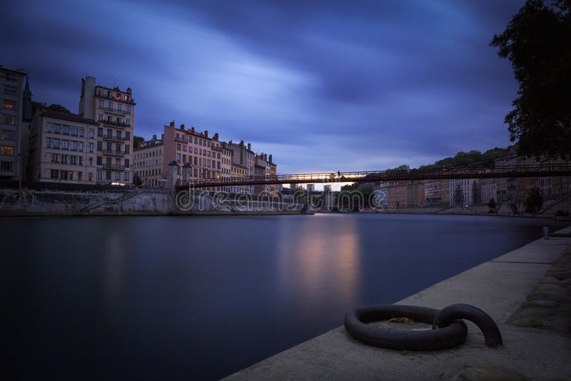Saone time. Woman looking at the Saone river from Passerelle Saint-Vincent in Lyon at dusk royalty free stock photography