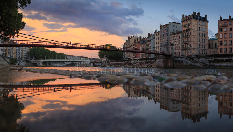 Saone view. Colorful sunset at an old footbridge over the Saone river, reflected in a puddle. Lyon, France royalty free stock photos