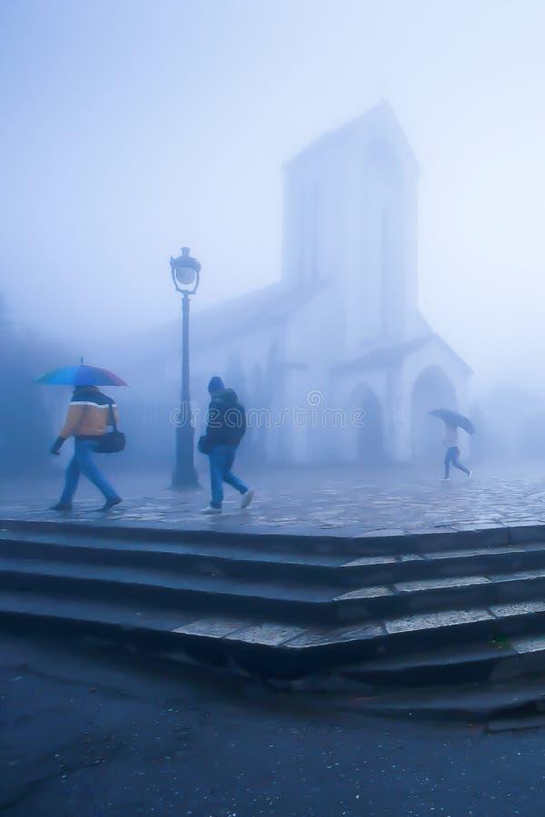 Sapa教会有薄雾的有雾的风景有伞的参观北越的教会的冬天早晨、越南语和游人的 免版税库存照片