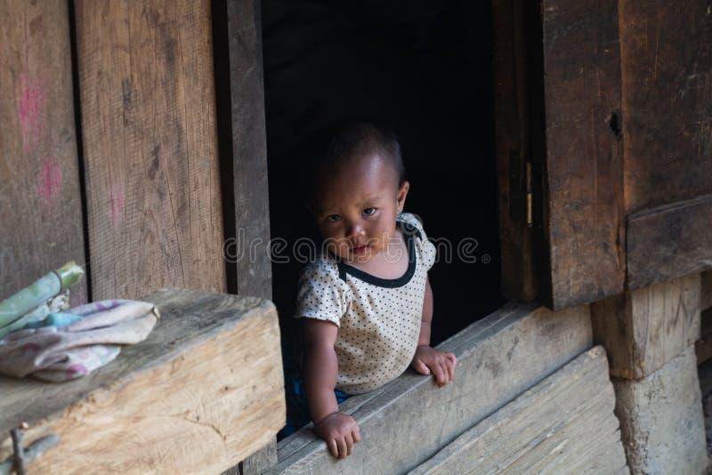 Sapa,越南- 2019年5月:看在木房子门廊的小孩 免版税库存图片