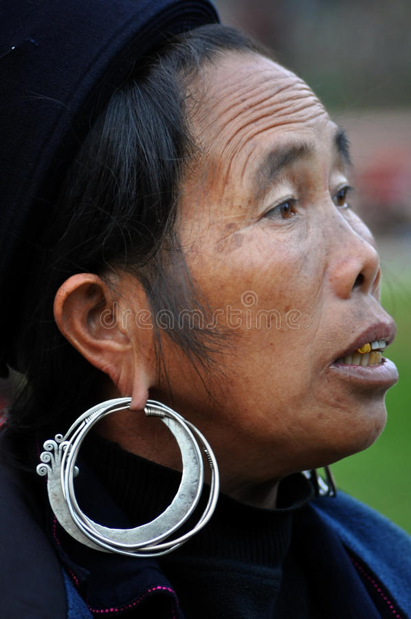 A woman from Black Hmong tribe in Sapa, Vietnam. SAPA – FEB 22: An unidentified old Black H'mong woman with a silver earring. The H'mong people are one of royalty free stock photo