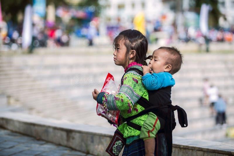 SAPA, ВЬЕТНАМ - 3-ЬЕ СЕНТЯБРЯ 2017: Азиатская маленькая девочка нося ее брата на улице в городке sapa стоковые фото