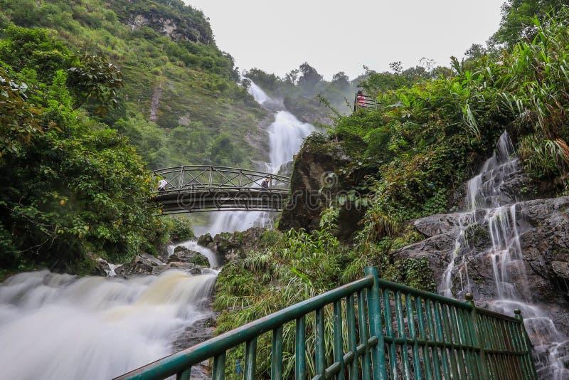 Sapa, провинция Lao Cai, северный Вьетнам на July13,2019: Сильная подача воды и стал-сдобренный мост на серебряном waterfa Bac Th стоковая фотография