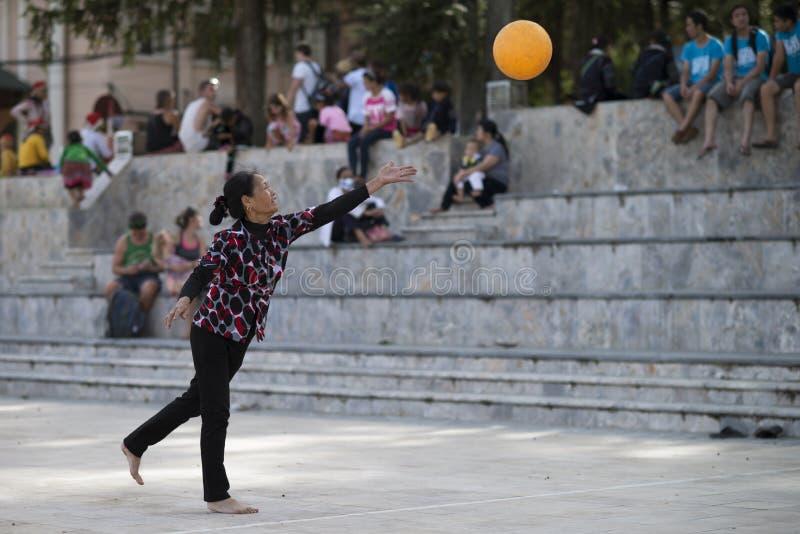Sapa Lao Cai, Vietnam - 08 17 2014: En barfota vietnamesisk portion- och spelavolleyboll för kvinna i Sa-PA, Lao Cai landskap, Vi arkivfoto