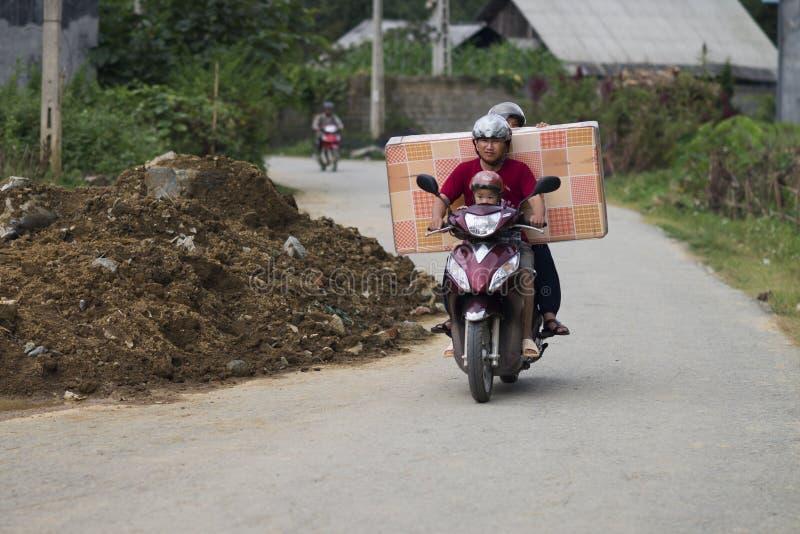 Sapa Lao Cai, Vietnam - 08 16 2014: Man med familjen som bär en madrass på en moped i SaPa Det vietnamesiska folket är van vid lo royaltyfri bild