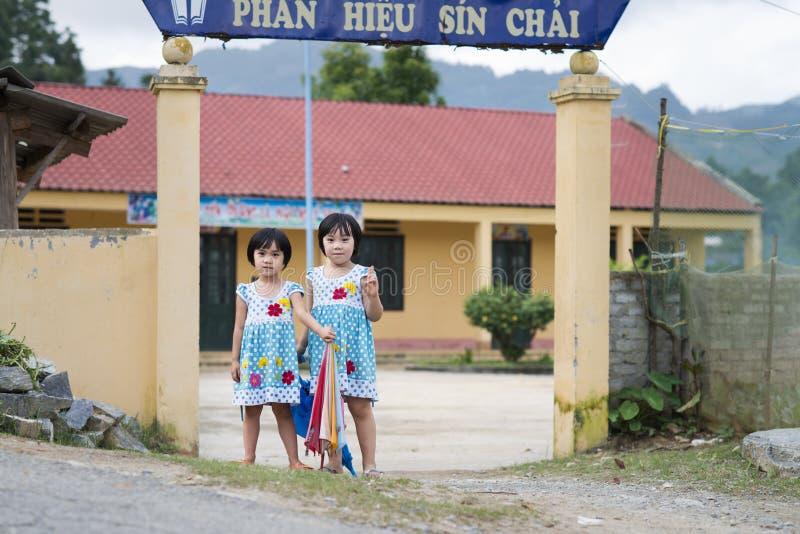 Sapa Lao Cai, Vietnam - 08 16 2014: Två lyckliga vietnamesiska skolflickor i likformig framme av en vietnamesisk grundskola för b arkivfoto