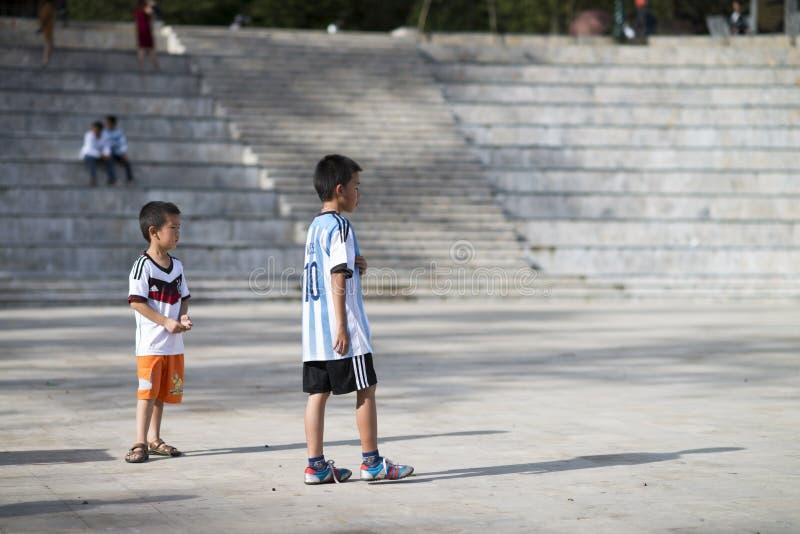 Sapa Lao Cai, Vietnam - 08 17 2014: Två vietnamesiska ungar som spelar fotboll med ärmlös tröjaskjortor av Tyskland och Argentina arkivfoton