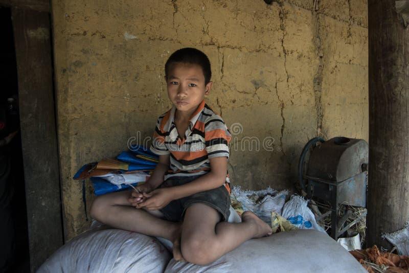 Sapa, Sep 2014 van Vietnam -14 - een Kind zit binnen voor zijn huis royalty-vrije stock afbeeldingen