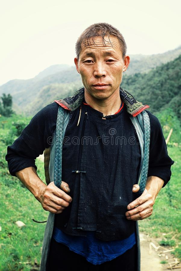 Black hmong tribe member man walking home after a long day work at his farm. Sapa/ Vietnam - AUG 5 2010: black hmong tribe member man walking home after a long royalty free stock photo