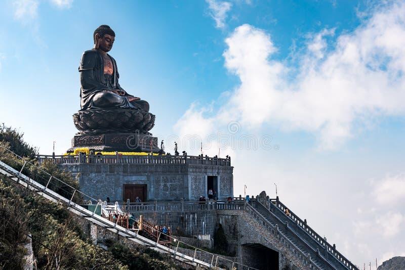 SAPA, VIETNAM - BRENG 14, 2019 IN DE WAR: Het reuzestandbeeld van Boedha op de bovenkant van Fansipan-bergpiek, blauwe hemel van  stock afbeelding