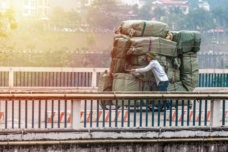 SAPA, VIETNAM - MARCH 14,2019 : In the morning Labor employed carriage a lot of  goods from the ship to another royalty free stock images