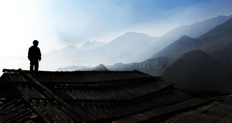Young boy standing on his house rooftop in his village, Sapa, Vietnam stock image