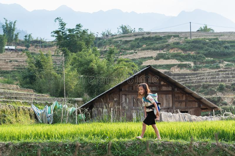 Sapa, Vietnam - May 2019: girl from Hmong ethnic group in traditional dress carries baby in a sling in Lao Cai province stock photo