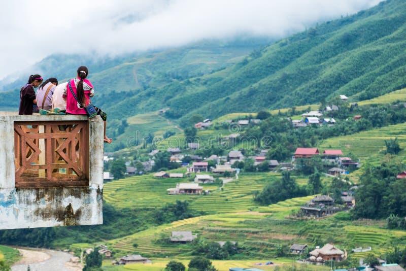 Sapa, Vietnam - 08 Sep 2017: Jonge de groepszitting van de meisjesstam op terras en meningsdorp op terrasvormige rijst royalty-vrije stock foto