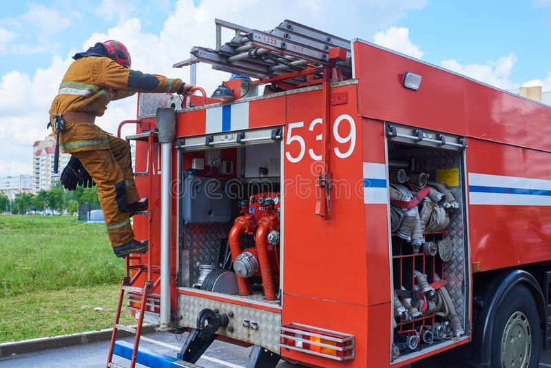 Sapador-bombeiro abaixo do carro de bombeiros nas escadas fotografia de stock