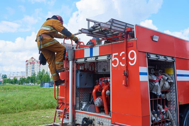 Sapador-bombeiro abaixo do carro de bombeiros nas escadas imagem de stock