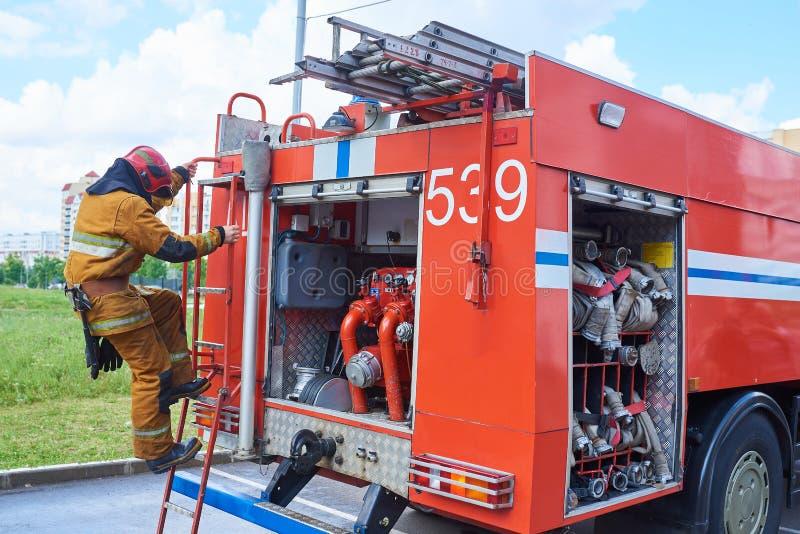 Sapador-bombeiro abaixo do carro de bombeiros nas escadas foto de stock royalty free