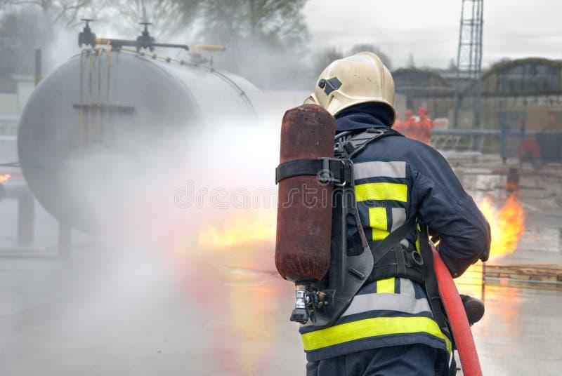Sapador-bombeiro que extingue o incêndio do tanque fotografia de stock royalty free