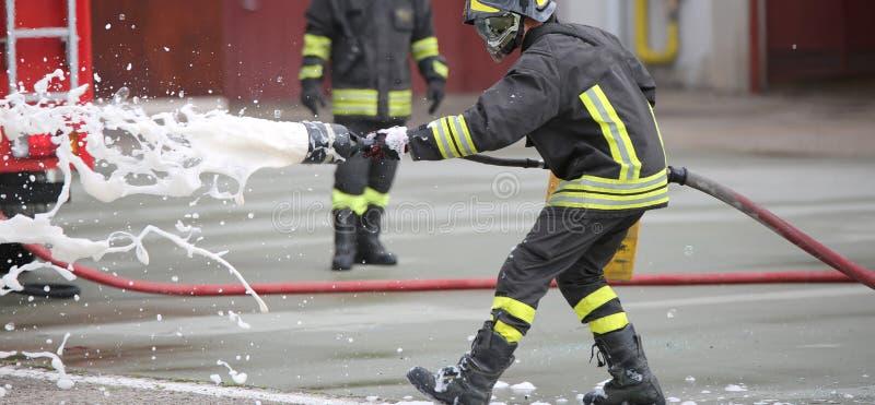 Sapadores-bombeiros ao extinguir o fogo com espuma fotos de stock royalty free