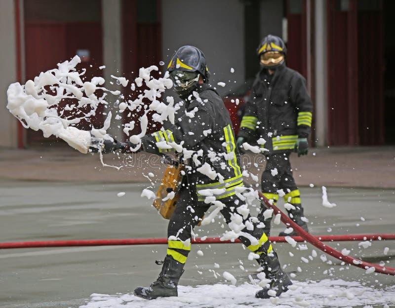 Sapadores-bombeiros ao extinguir o fogo com espuma foto de stock royalty free