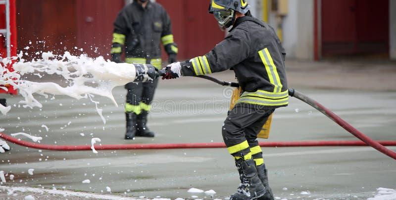 Sapadores-bombeiros ao extinguir o fogo com espuma imagens de stock royalty free
