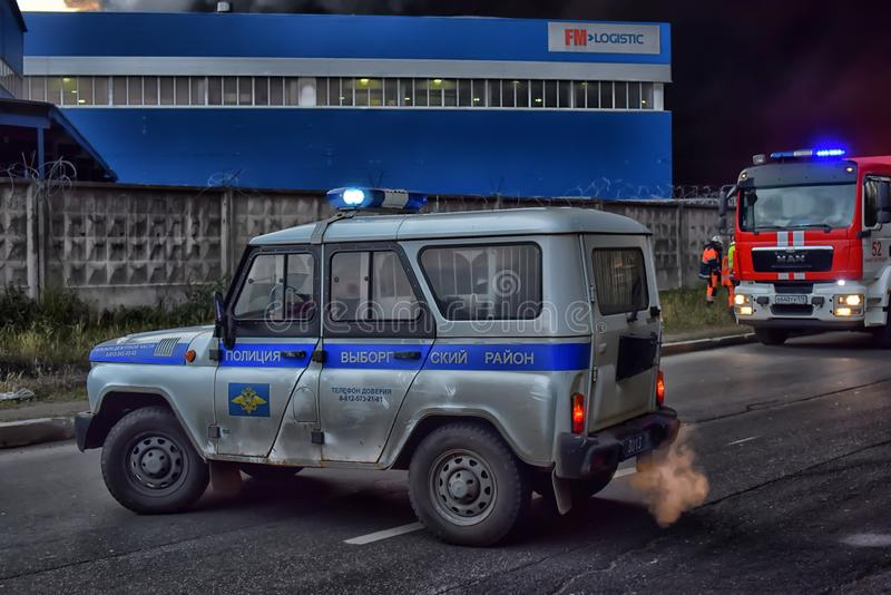 Sapadores-bombeiros e carros de polícia no fogo - extinguindo na zona industrial imagens de stock royalty free