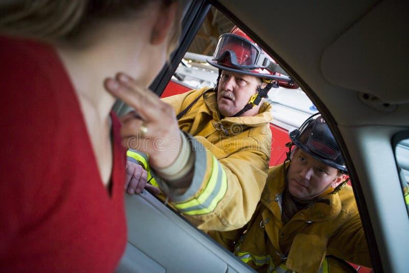 Sapadores-bombeiros que ajudam uma mulher ferida em um carro fotos de stock