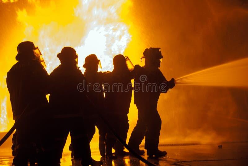 Sapadores-bombeiros que controlam a água de pulverização da mangueira durante o exercício de combate ao fogo imagens de stock