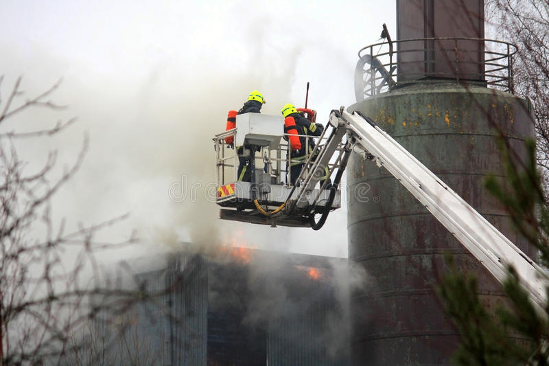 Sapadores-bombeiros que extinguem o fogo em Crane Platform hidráulico fotos de stock