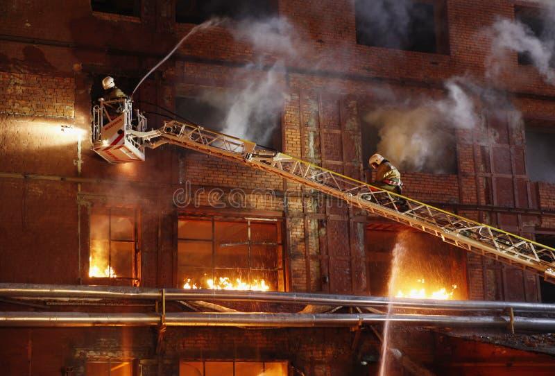 Sapadores-bombeiros que lutam um incêndio fotos de stock