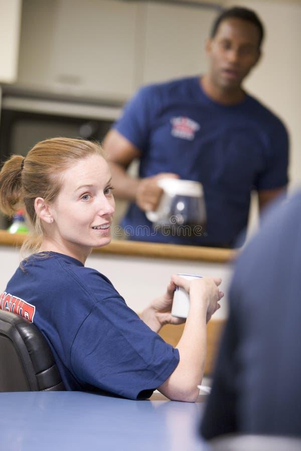Sapadores-bombeiros que relaxam na cozinha da equipe de funcionários imagem de stock