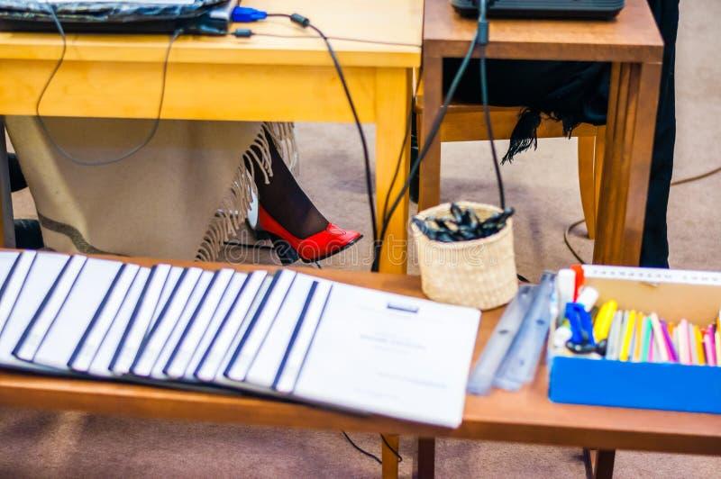 A sapata da mulher vermelha com calças justas pretas cola para fora de debaixo da tabela cercada por acessórios do escritório com foto de stock royalty free